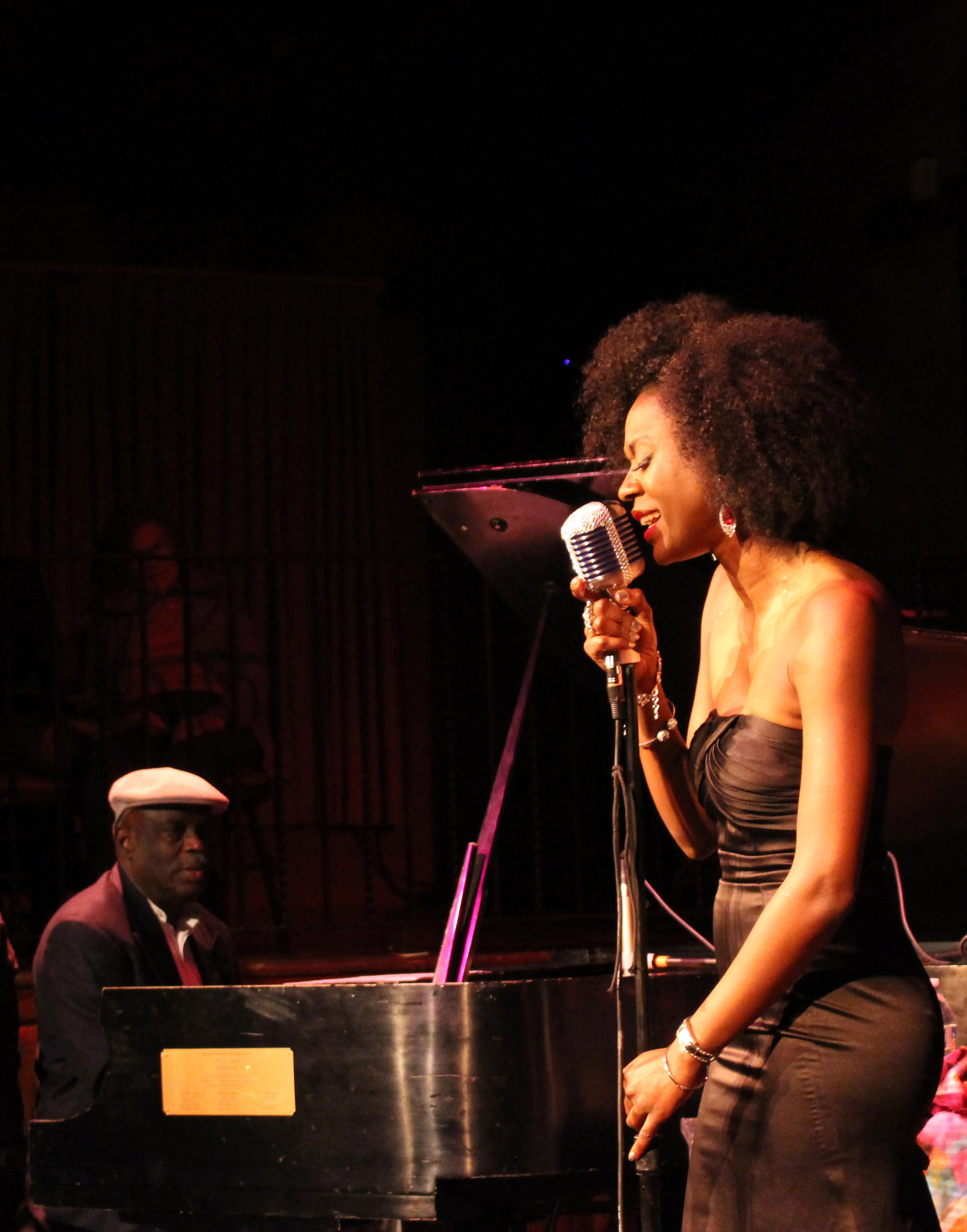 Nayo Jones sings at microphone during live show.