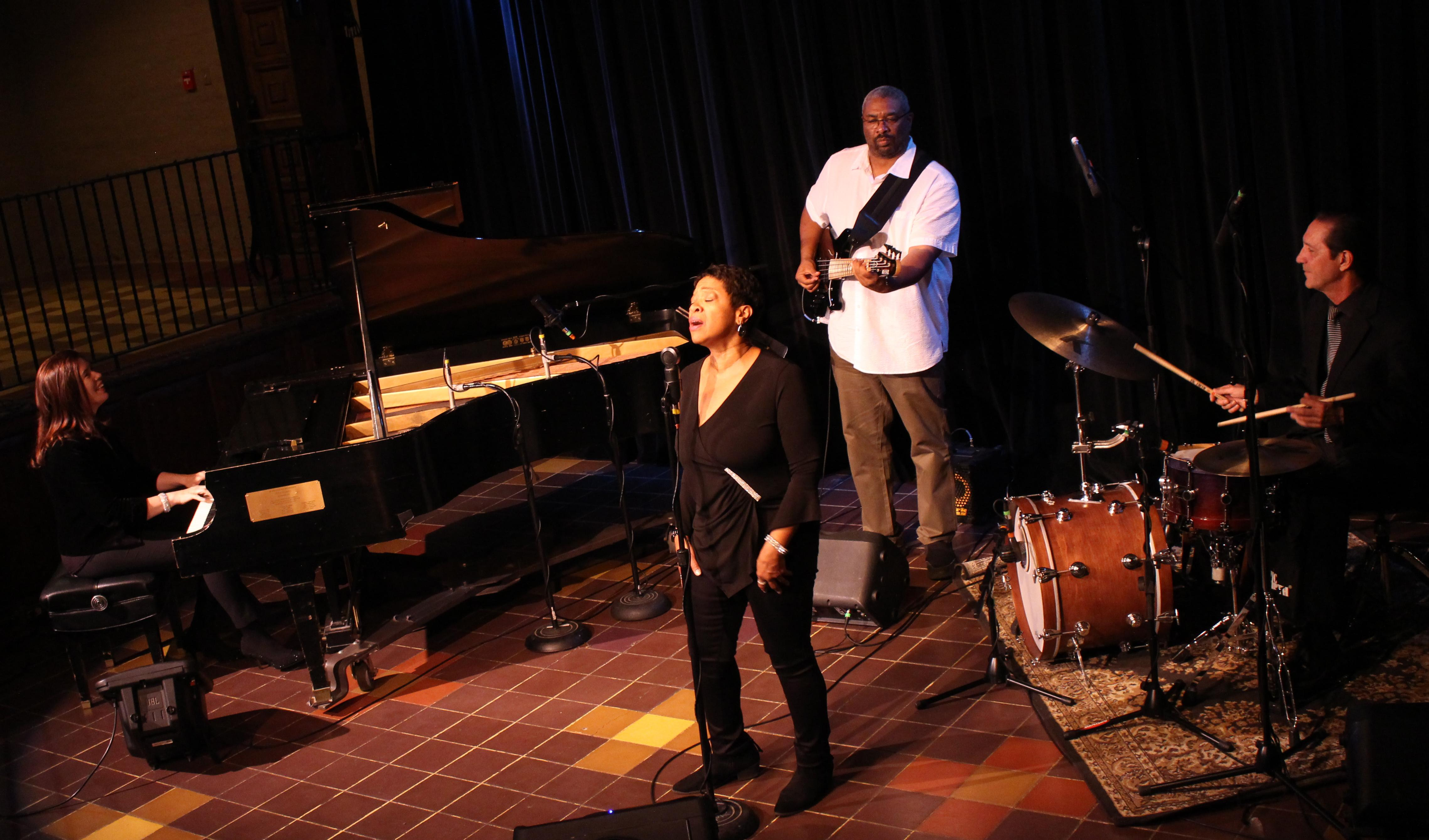 Pianist, vocalist, bassist and drummer jam on stage.